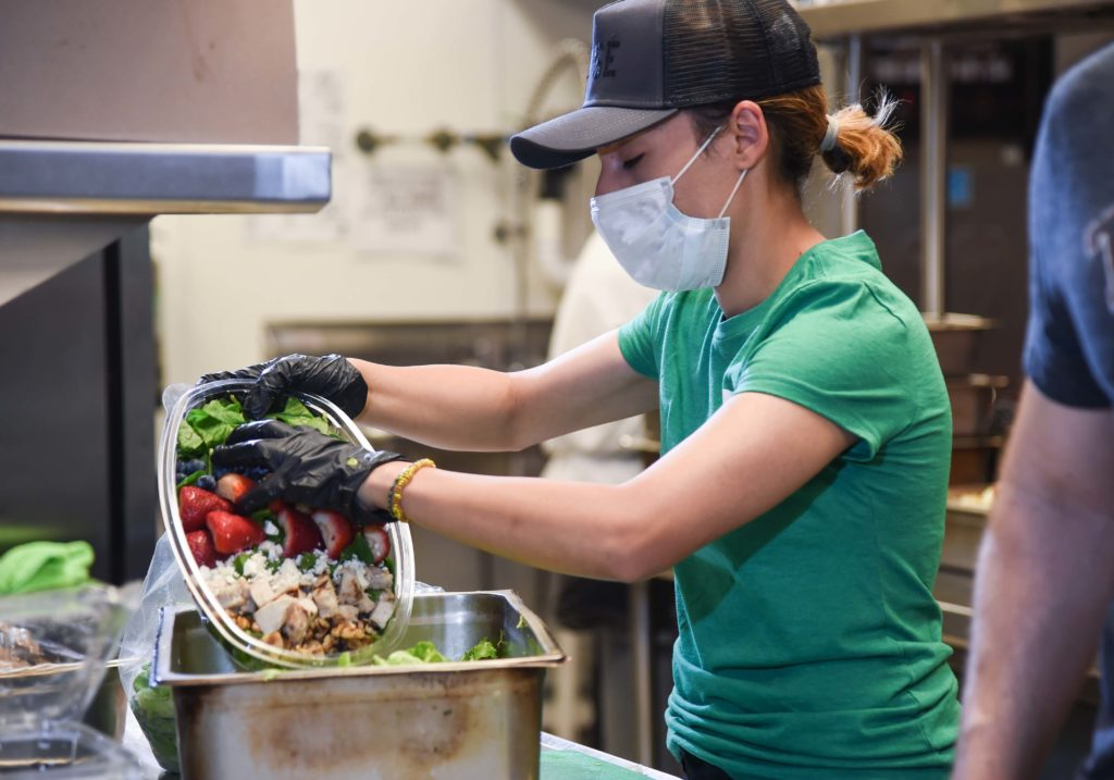 Woman in mask preparing food
